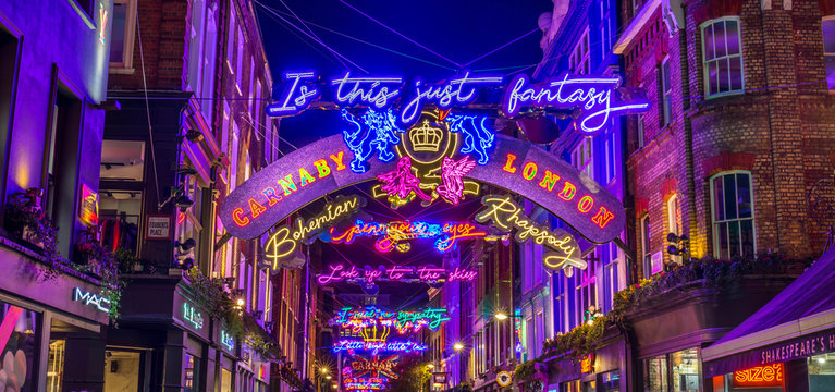 Lights down Carnaby Street in London during the Christmas Season. Large amounts of people can be seen.
