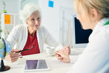Smiling confident senior lady in white cardigan sitting at table and holding eyeglasses while talking to trip manager and choosing travel tour at meeting in office.