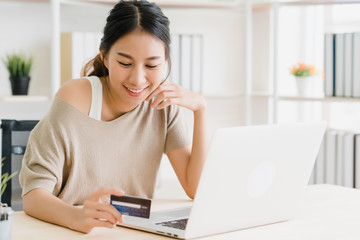 Beautiful Asian woman using computer or laptop buying online shopping by credit card while wear sweater sitting on desk in living room at home. Lifestyle woman at home concept.