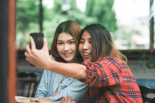 Beautiful happy Asian women lesbian lgbt couple sitting each side eating a plate of Italian seafood spaghetti and french Fries at restaurant or cafe. Female couple using smartphone for selfie.