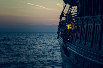 In de dag Schip yellow illumination from soft focus vintage lamp in over board of wooden old pirate ship on sea surface landscape with horizon line in evening dark twilight time