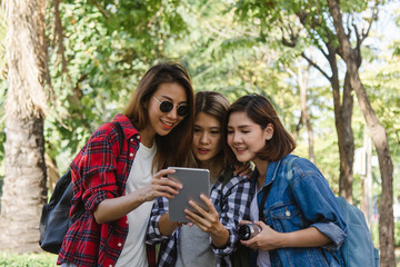 Group of Asian women using camera to make photo while traveling at park in urban city in Bangkok, Thailand. Lifestyle beautiful friends tourist travel holiday in Thailand concept.