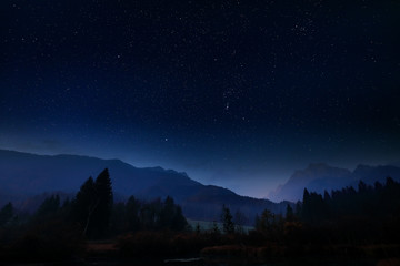 Night landscape with dark sky and stars in Slovenia, nature in Europe.  Foggy Triglav Alps with forest, travel in Slovenia. Beautiful night with blue sky.