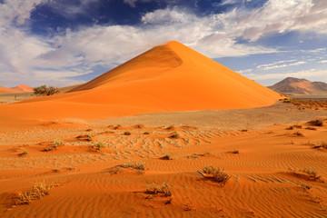 Grote oranje duin met blauwe lucht en wolken, Sossusvlei, Namib-woestijn, Namibië, Zuidelijk Afrika. Rood zand, grootste duin ter wereld. Reizen in Namibië.
