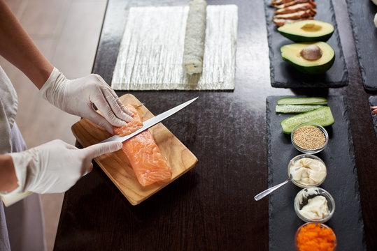Close-up view of process of preparing delicious rolling sushi in restaurant. Female hands in disposable gloves slicing salmon. Avocado, cucumber, fish, sauces on the black stone plates