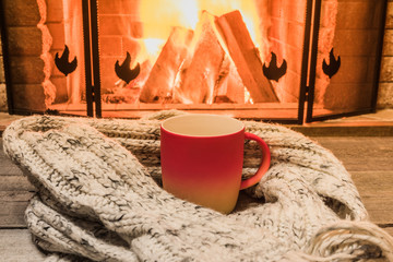 Cozy scene near fireplace with a Red cup with hot tea and cozy warm scarf.