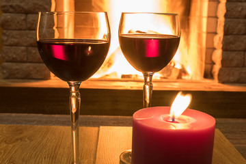 Two glasses of red wine and candle near cozy fireplace, in country house, winter vacation, horizontal.