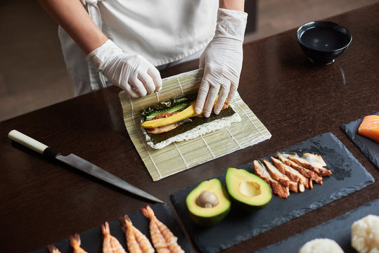 Master is making a sushi roll with nori, rice, cucumber, eel and omelet using bamboo mat. Closeup view of process of cooking sushi