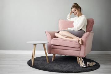 Attractive fashionable young European female with hair bun and bare feet sitting comfortably in pinkish armchair and smiling, enjoying spare time on her own, stylish high heeled shoes on carpet