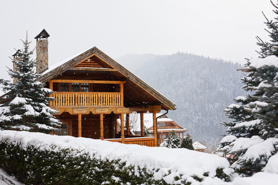 Christmas wooden mansion in mountains on snowfall winter day. Cozy chalet on ski resort near pine forest. Cottage of round timber with wooden balcony. Fir-trees covered with snow. Chimneys of stone.
