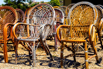 Many old wicker chairs stand in the open. Concept - old furniture