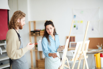 Young woman with palette pointing at her groupmate painting on easel during lesson