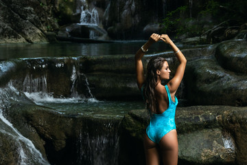 Young and sexy woman on the beautiful waterfall in the jungle