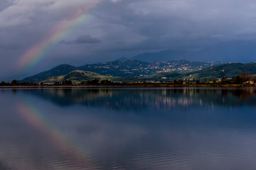 The rainbow is reflected in the waters of Lake Massaciuccoli, Lucca, Tuscany, Italy