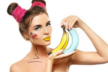 Beautiful model with creative pop art makeup holding bananas