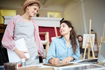 Two friendly girls looking at each other while consulting or discussing working moments in studio