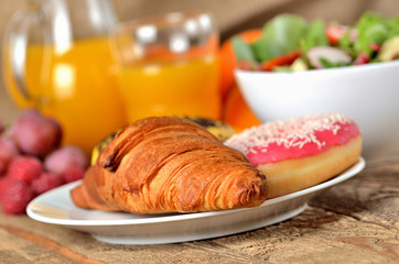 Close-up of croissant and donuts, orange juice and fresh salad - breakfast on wooden table