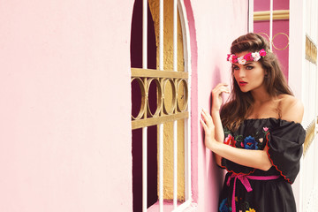 Beautiful woman wearing traditional mexican dress is posing beside pink wall