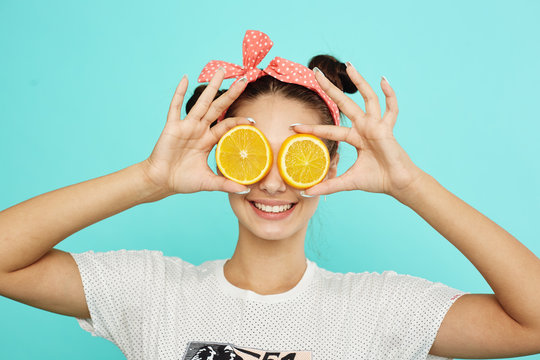 Young funny girl with pink bow on her head holds orange slices on place of her eyes on the blue background in the studio