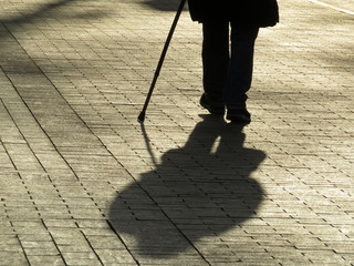Silhouette of man walking with a cane, long shadow on pavement. Concept of blind person, disability, old age, diseases of the spine