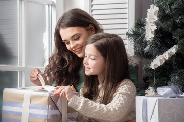 Mother and daughter unwrapping gift