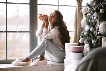 Nice dark-haired girl dressed in pants, sweater and warm slippers holds a red cup sitting on the windowsill of a panoramic window in the room next to the New Year tree and gifts
