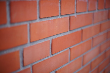Perspective of a red brick wall, selective focus.