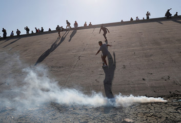 Migrants, part of a caravan of thousands traveling from Central America en route to the United States, run away from tear gas thrown by the U.S. border control near the border wall between the U.S and Mexico in Tijuana