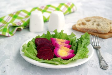 White plate with appetizers, pickled eggs and spicy beets on green salad leaves. Served with fresh wheat bread.