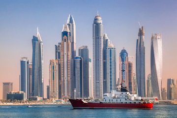 Panorama of Dubai with ship against skyscrapers in UAE