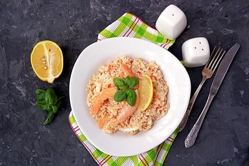 Rice with squid and shrimp in a white plate on a dark gray background. Served with a slice of lemon. Top view.