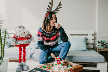 .Sweet and cheerful woman enjoying christmas at her home. Wearing christmas costume and eating tipical sweets. Lifestyle. Season photography.