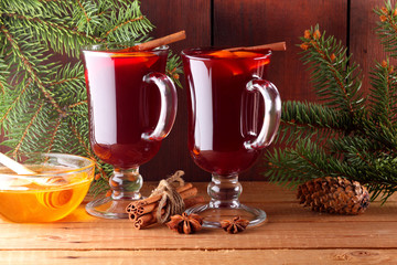 Mulled wine and Christmas tree branches on wooden boards. Christmas mulled wine, cinnamon sticks, anise and honey. Alcoholic drink of wine, fruit and honey. Festive drink on wooden boards