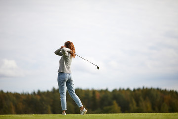 Young woman in activewear holding golf club after hitting ball while standing on the field