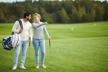 Young woman showing her boyfriend nice place for playing golf while both standing on large green field