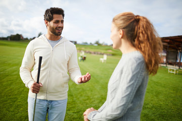 Young man in white hoodie and blue jeans explaining his girlfriend or golfer some play stuff
