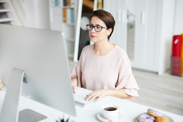 Young elegant businesswoman looking at computer screen while networking by desk in office