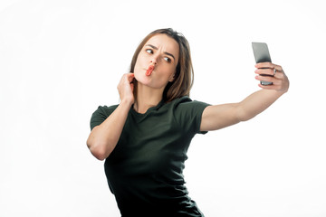 Pretty girl makes her lips duck and take a self portrait with her smart phone. Cute lovely young woman making duck face and taking selfie with mobile phone over white background.