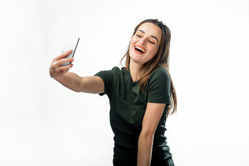 Happy flirting young girl taking pictures of herself through cell phone, over white background. Beautiful smiling girl with long hair making selfie.