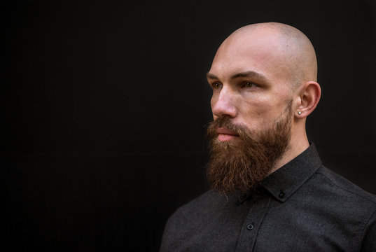 bald man with a beard in a black shirt on a dark background