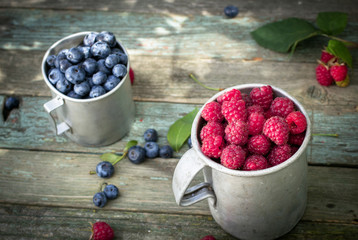 Mugs of raspberry and blueberry on wooden table outdoors