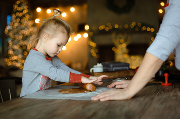 Grandma helps her granddaughter roll out the dough for a traditional Christmas ginger cookie. Cook together in a house decorated with a Christmas tree and garlands. Family friendly Christmas concept.