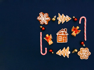 Christmas gingerbread Flat lay photo Geometric composition of gingerbreads in different shapes with small colourful baubles and candy sticks on dark blue background Poster template with copy space