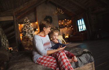 Grandma and granddaughter have fun together reading a book on the bed . Family Christmas concept.