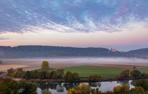 Morning view on castle Guttenberg, Haßmersheim, and river Neckar with fog in the fields from castle Horneck, Gundelsheim, Germany