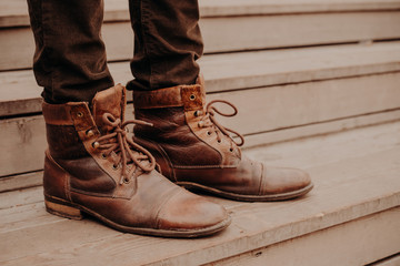 Image of mans brown footwear standing on wooden steps. Male in trousers and shaggy shoes on threshold. Horizontal view
