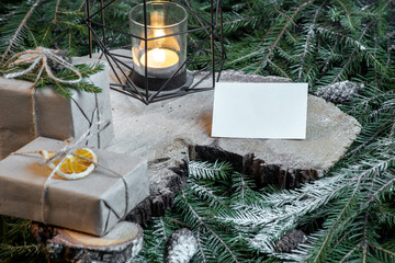 Blank business card on christmas tree branches, new year decor and gift boxes.