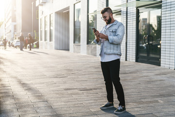 Handsome smiling hipster businessman with beard, in denim jacket, trendy glasses walks around city and using smartphone.