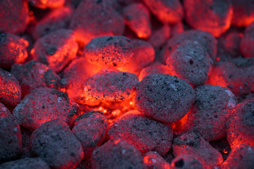Coals smolder and glow. Residual flame from smoldering coals in cinder, closeup view. Flicker of burning coals at night.