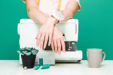 Sewing workshop. Close-up of seamstress hands on a colored background.